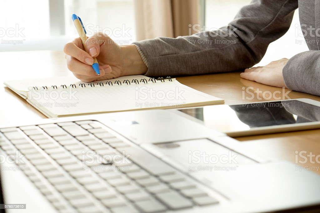 working woman writing on paper and typing on laptop stock photo