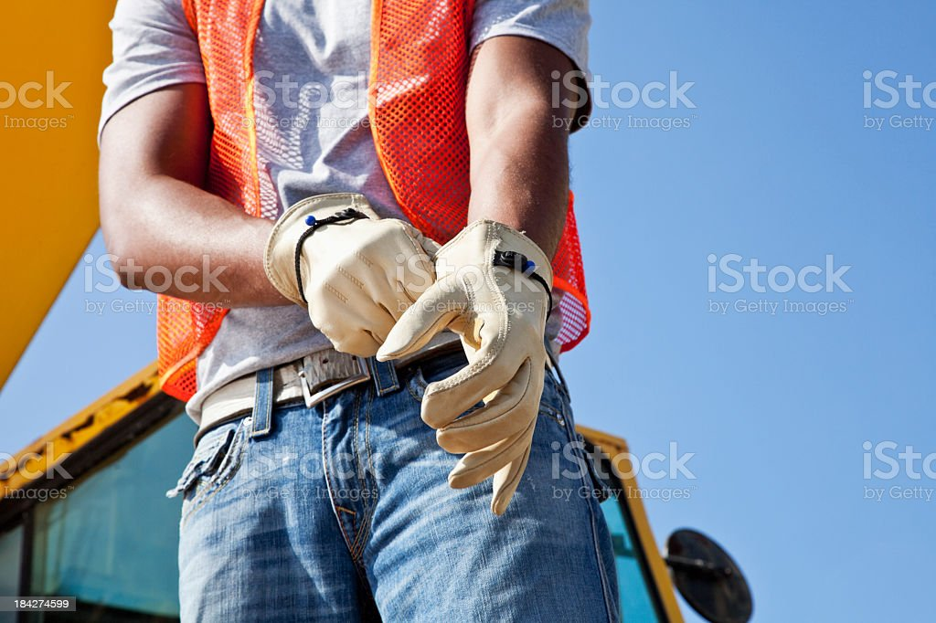 Workman at construction site putting on gloves stock photo
