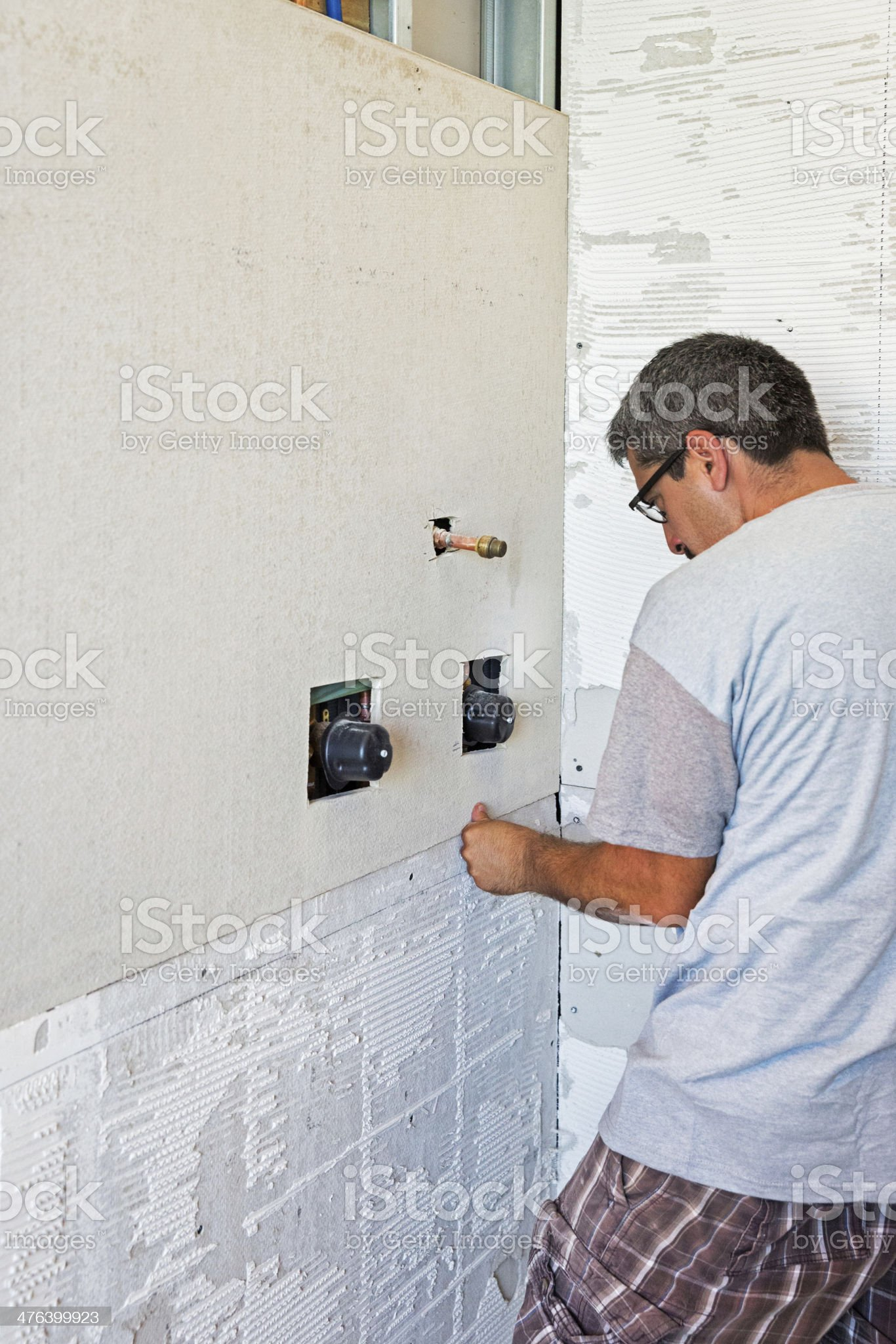 Workman constructing a bathroom shower stall royalty-free stock photo