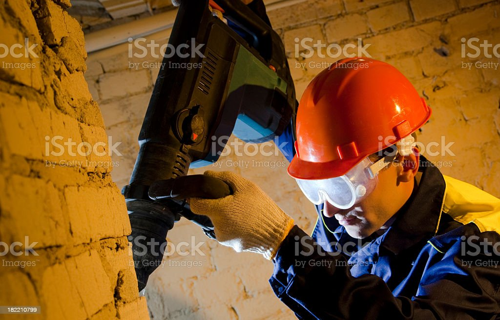 Workman hold perforator and drilling brick wall royalty-free stock photo