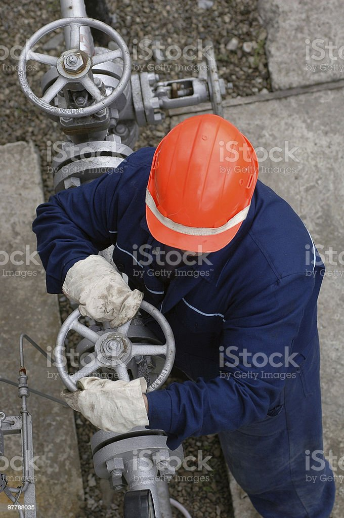 A workman in a hard hat using pipeline equipment  royalty-free stock photo
