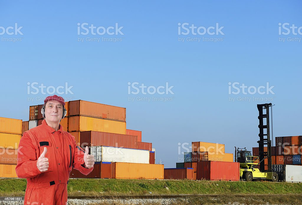 Workman in Front of Containers stock photo
