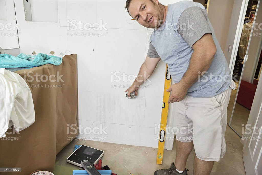 Workman points to spot on bathroom wall royalty-free stock photo