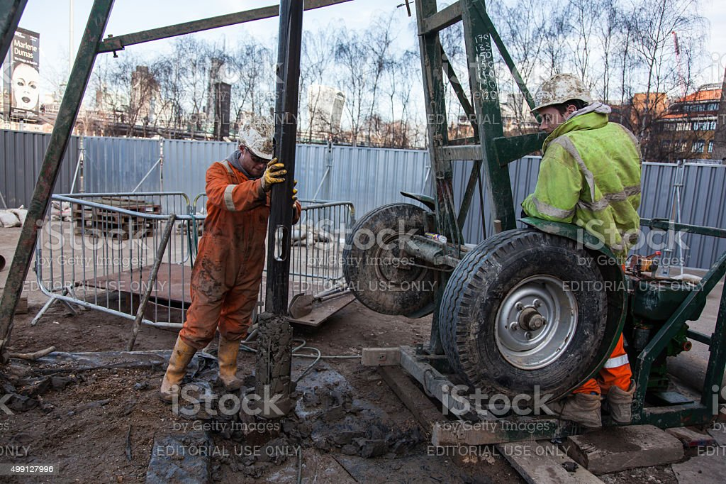 Workman pushes drill bit way borehole in London stock photo