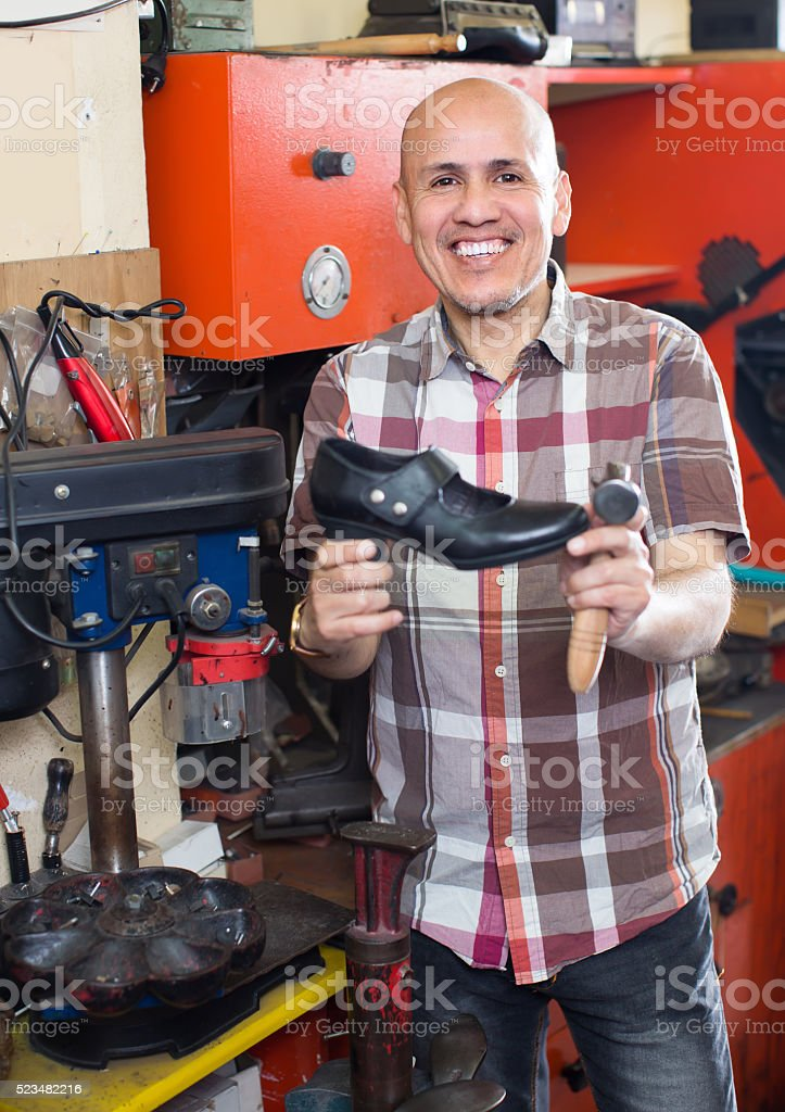 Workman repairing pair of shoes stock photo