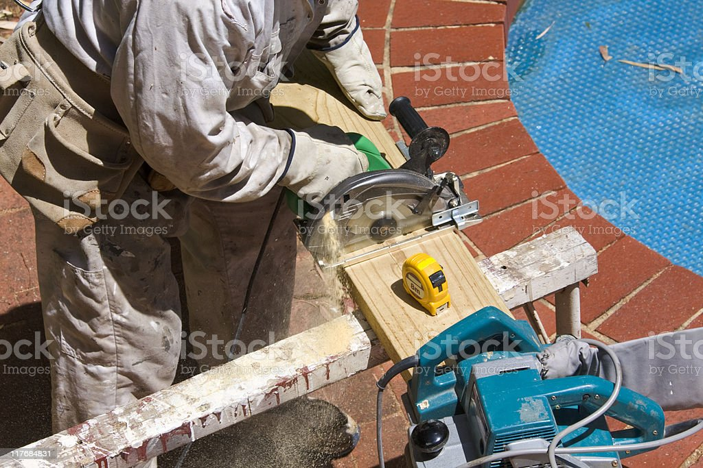 Workman sawing wood with a circular saw royalty-free stock photo