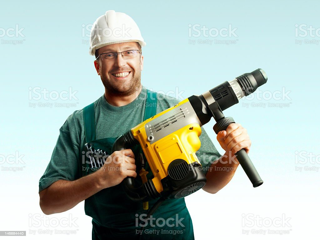 Workman smiling wearing safety helmet holding a perforator royalty-free stock photo