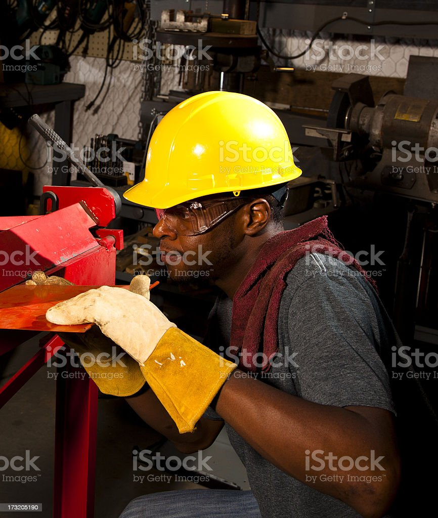 Workman wearing hardhat, goggles and safety gloves in workshop royalty-free stock photo