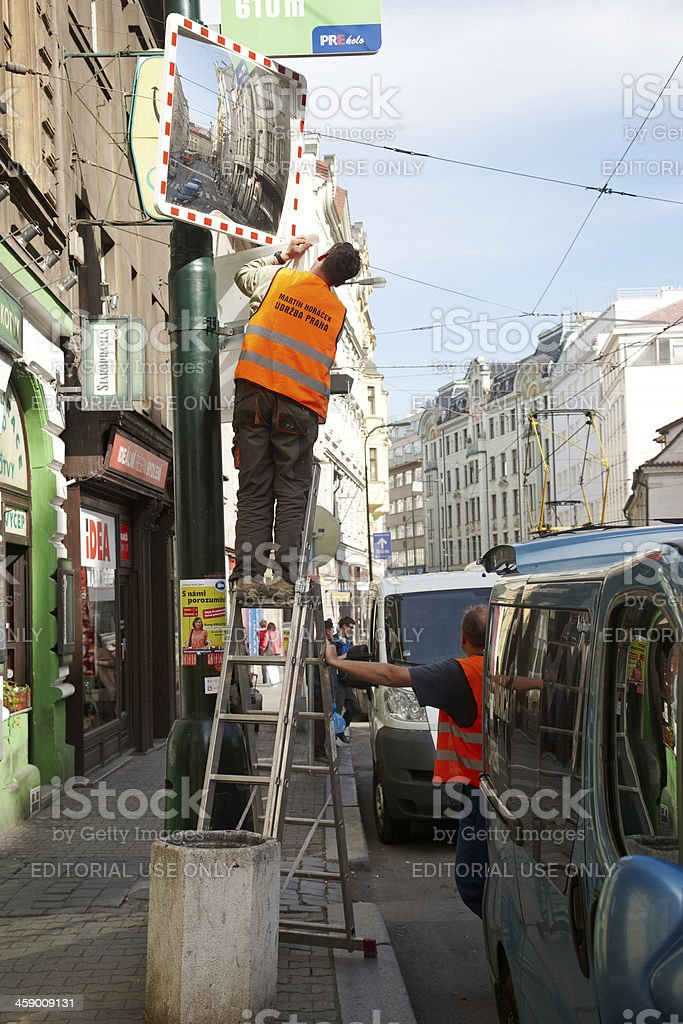 Workmen cleaning traffic mirror in Prague royalty-free stock photo