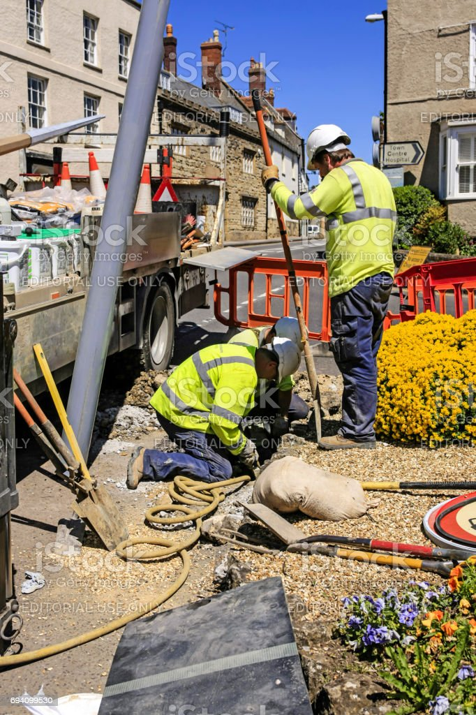 Workmen digging a foundation and wire routing trough to install new street lighting poles in Sherborne, Dorset UK stock photo