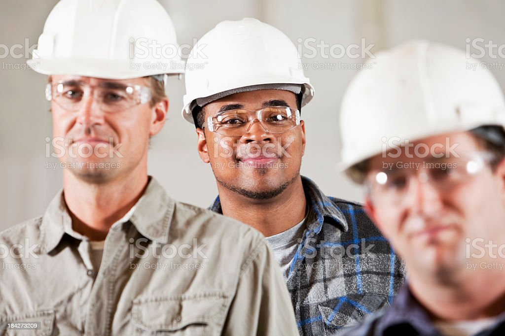 Workmen in hardhats and safety glasses stock photo