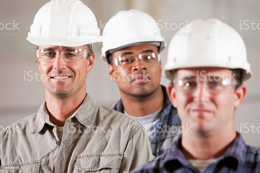 Workmen in hardhats and safety glasses royalty-free stock photo