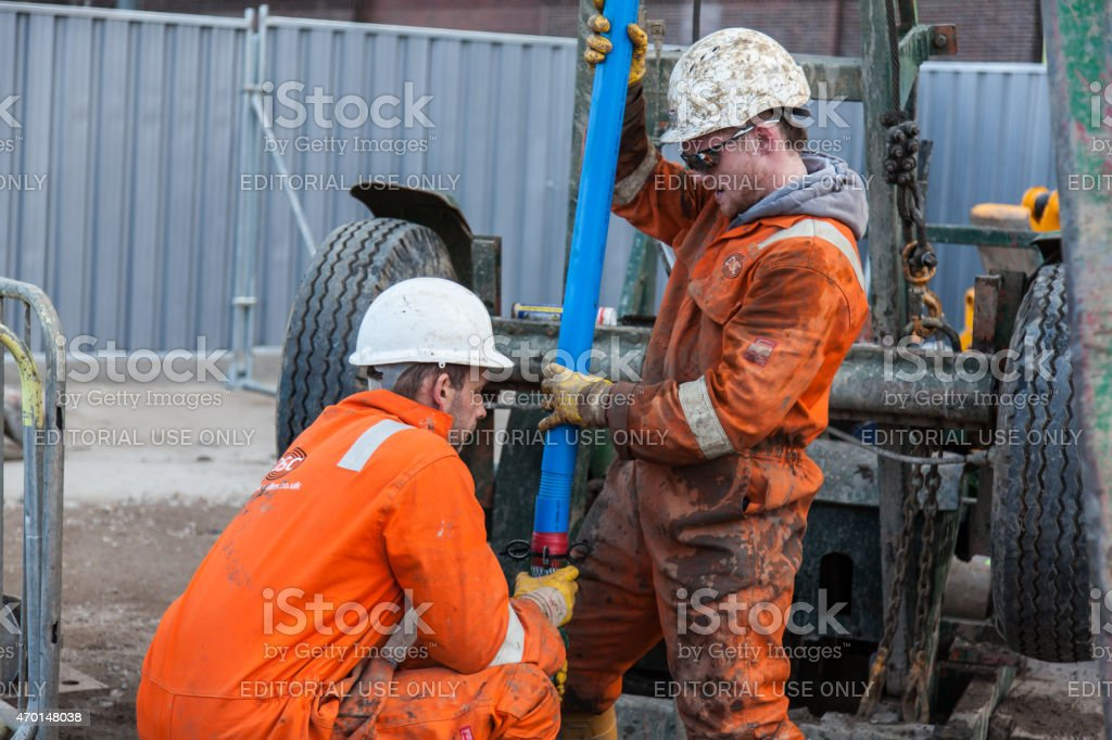 Workmen in orange overalls and white hardhats stock photo