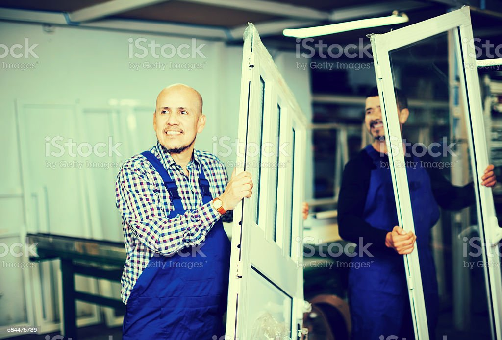 Workmen inspecting PVC manufacturing output stock photo