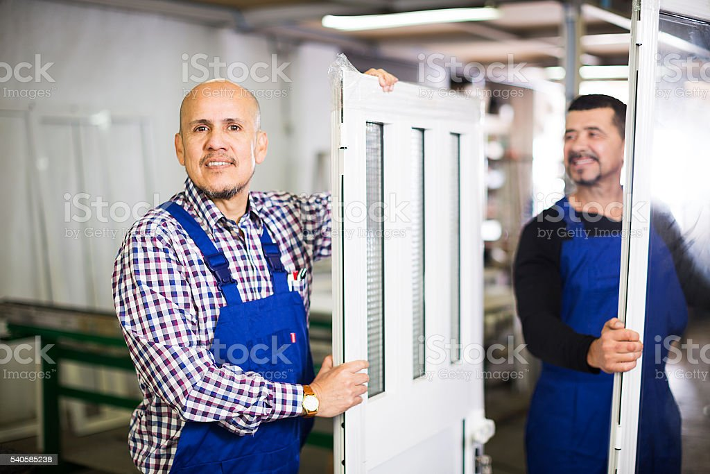 workmen with finished PVC profiles stock photo
