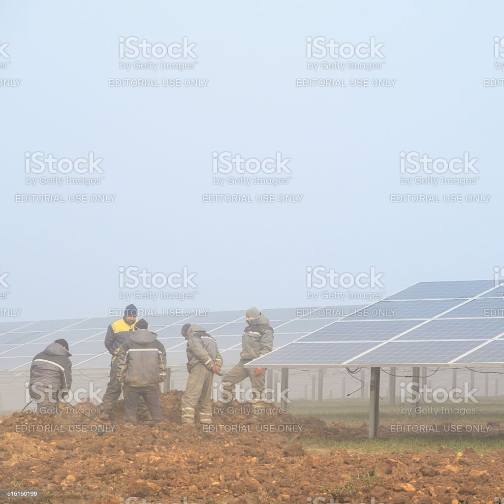 Workmen working at a solar energy farm stock photo