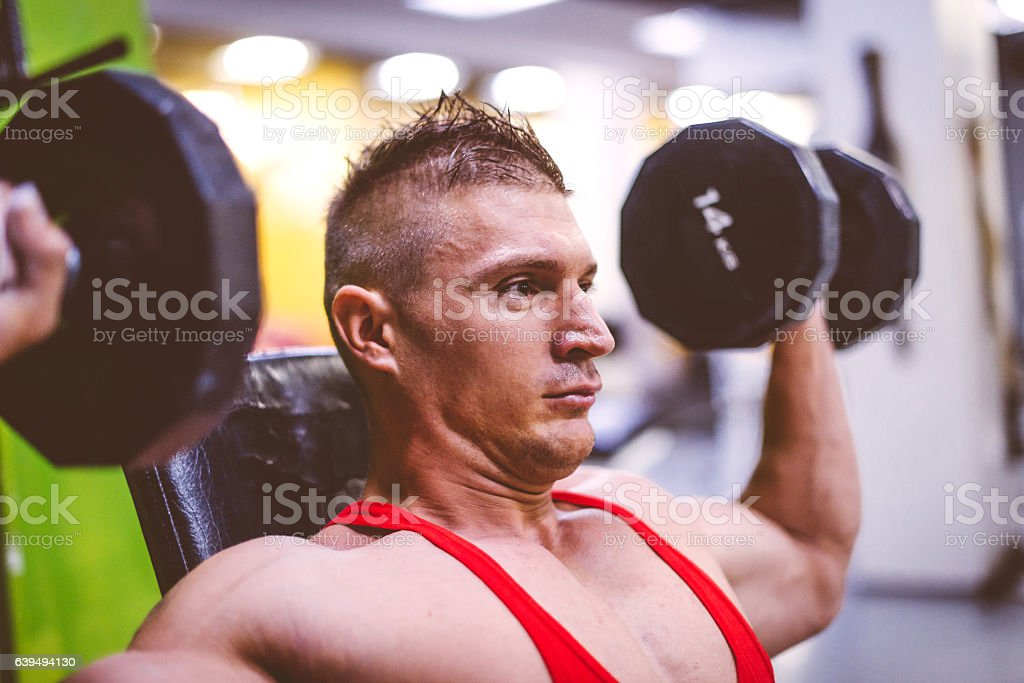 Workout in gym, exercising shoulders stock photo