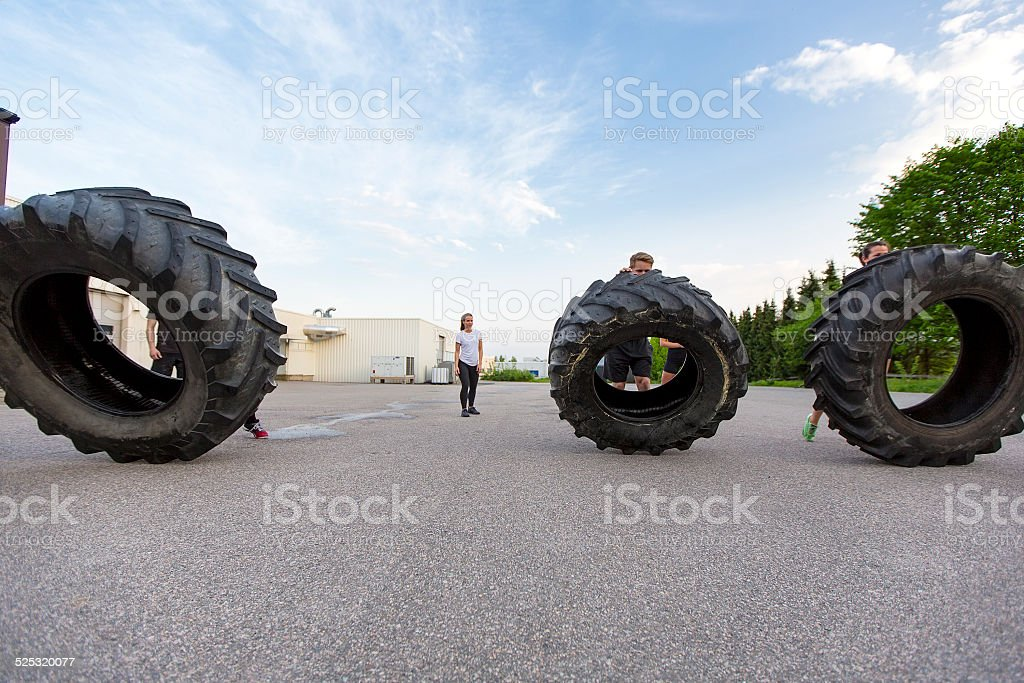 Workout team flipping heavy tires outdoor stock photo