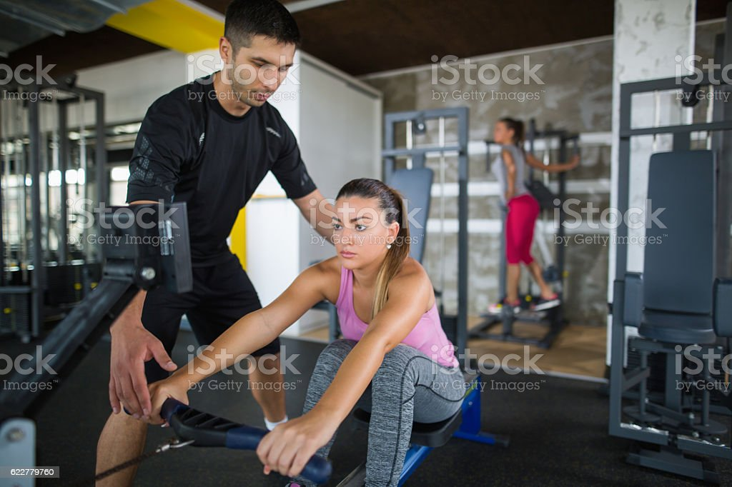Workout with personal trainer on rowing machine at gym. stock photo