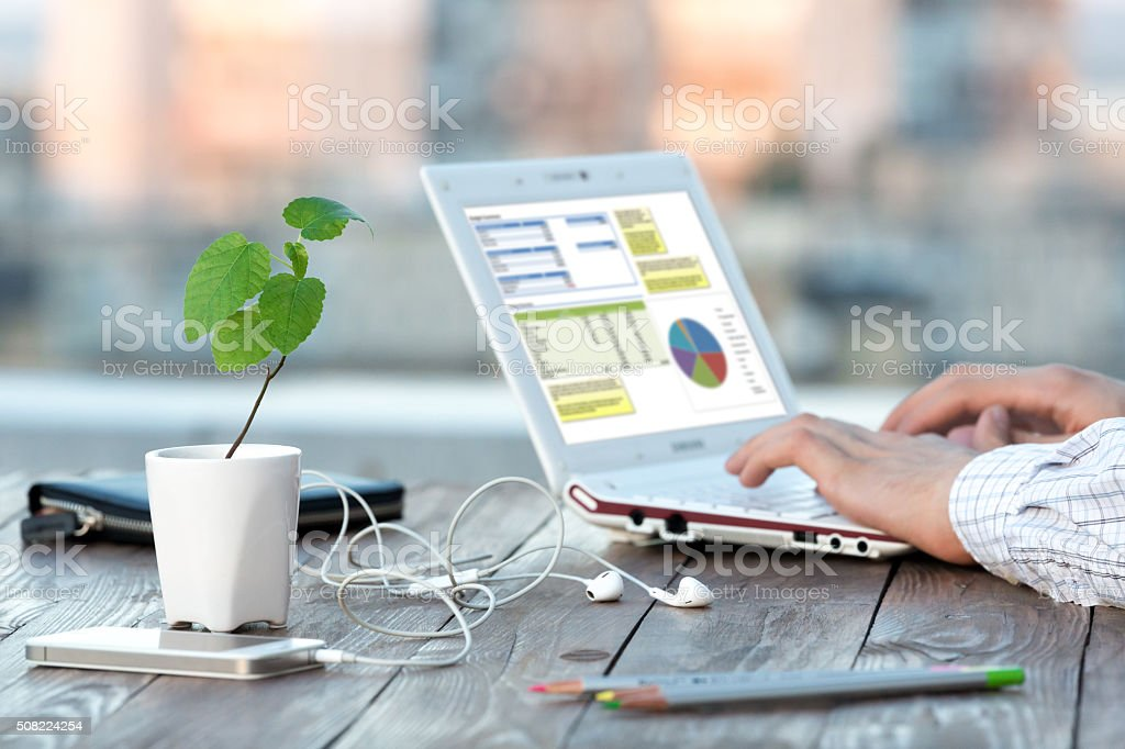 Workplace at Outdoor Patio at wooden Table Computer and Flower stock photo