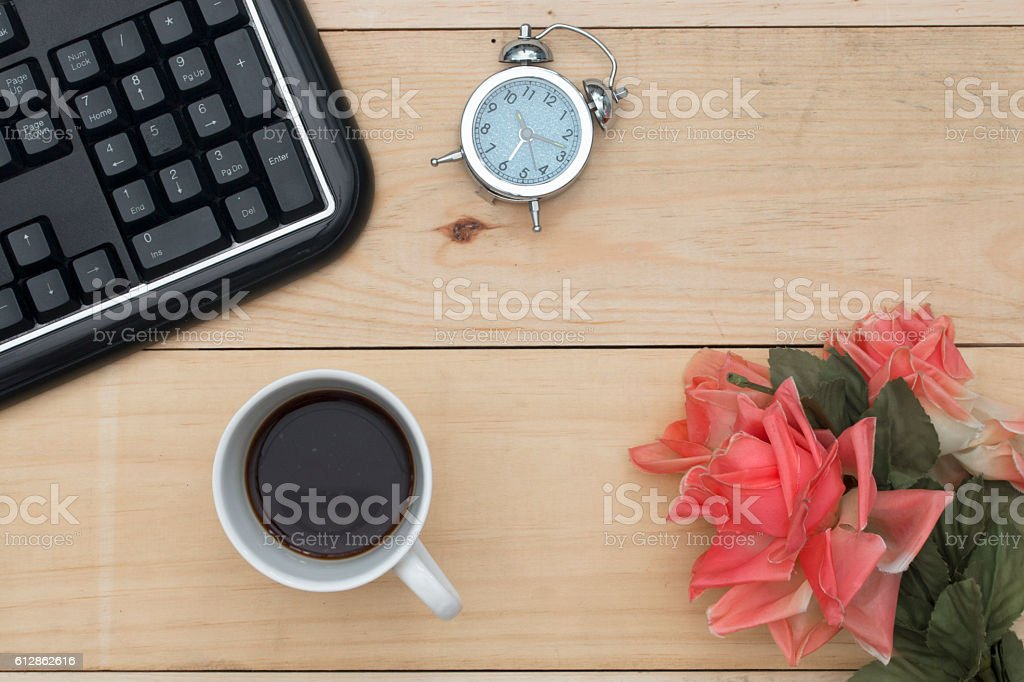 Workplace with keyboard, alarm clock, coffee and flowers on wood stock photo