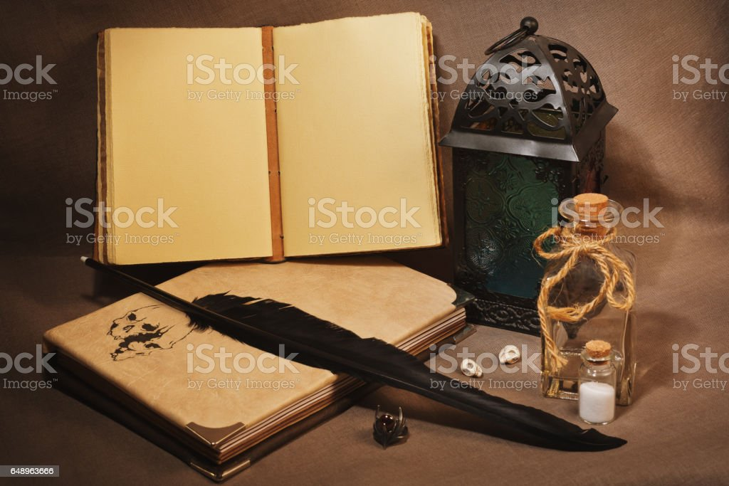 Workspace of the witch or sorcerer with old grimoires, charms and lantern stock photo