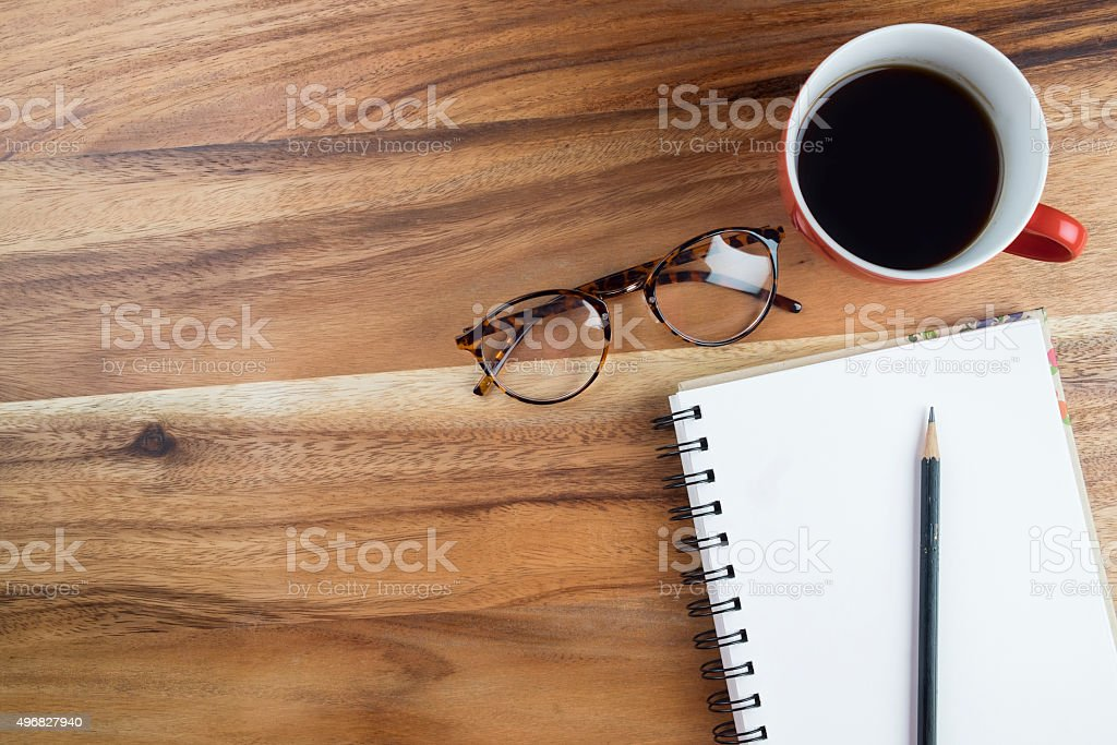 Workspace with coffee cup, instant photos, note paper and notebook on...