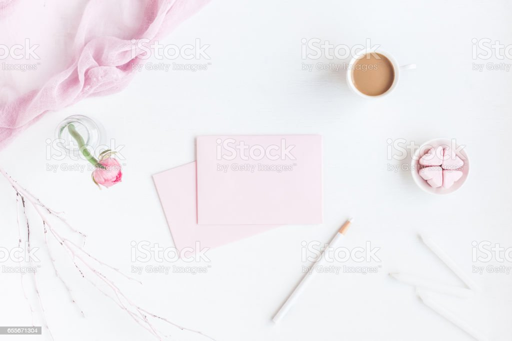 Feminine workspace with notebook, cup of coffee, paper blank, pink...