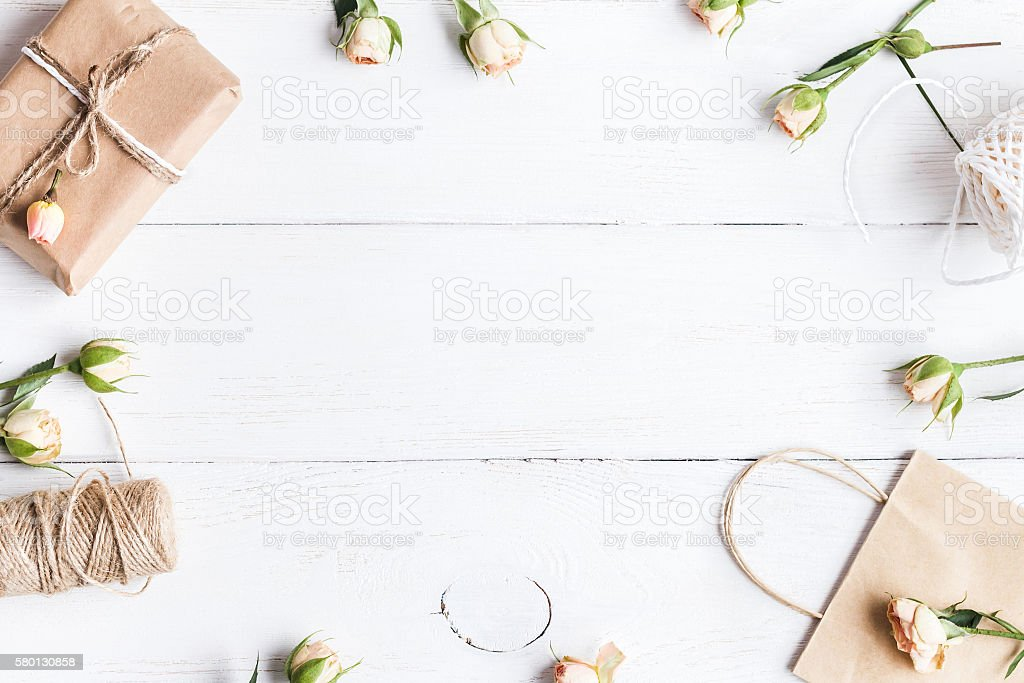 Workspace with rose flowers, gift, paper bags. Creation. flat lay stock photo