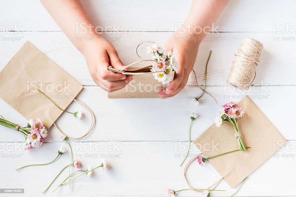 Workspace with small bouquets of daisy flowers. Flat lay stock photo