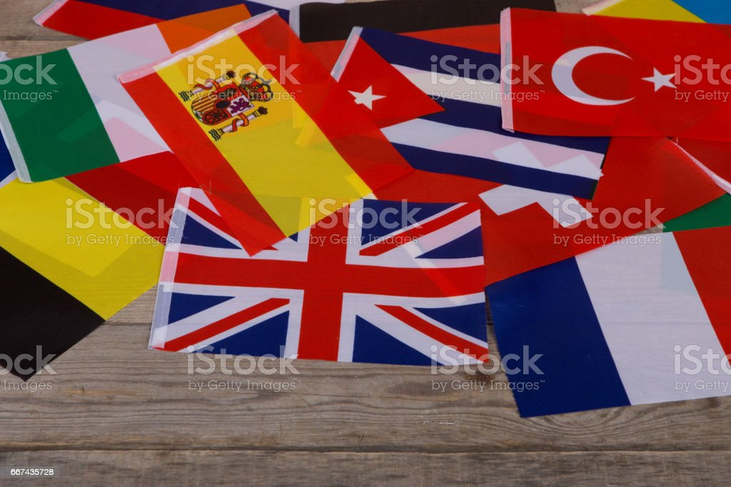 World flags, little flags of different countries on wooden table stock photo