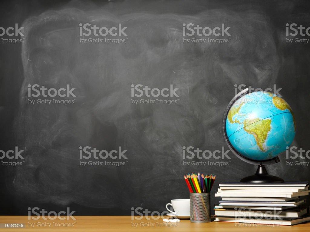 World globe on books on school teacher's desk stock photo