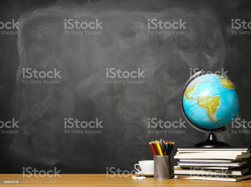 World globe on books on school teacher's desk stock photo