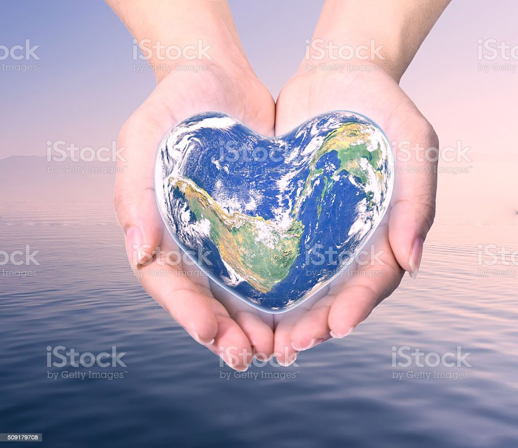 World in heart shape with over women human hands stock photo