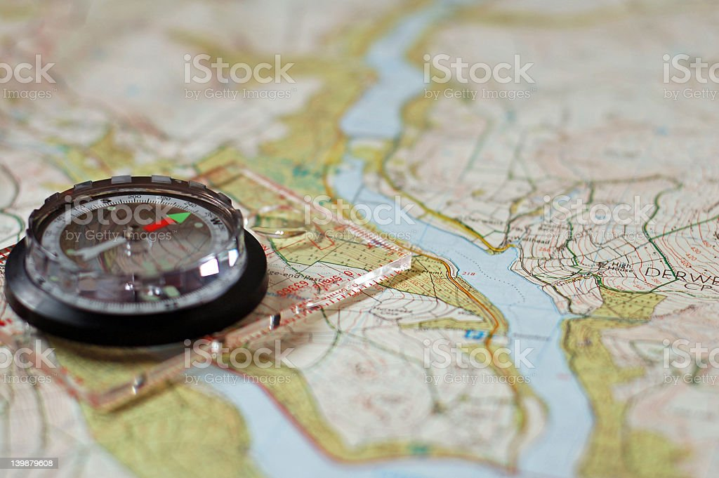 A world map atlas and a working compass royalty-free stock photo