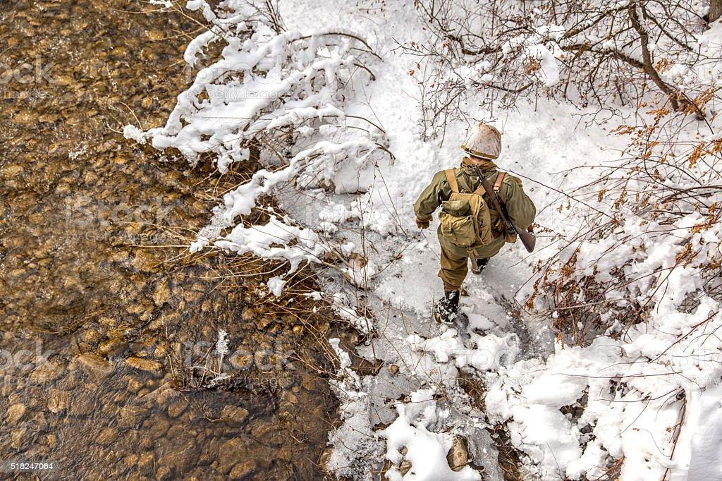 World War II: Soldier Crossing Creek in the Snow stock photo