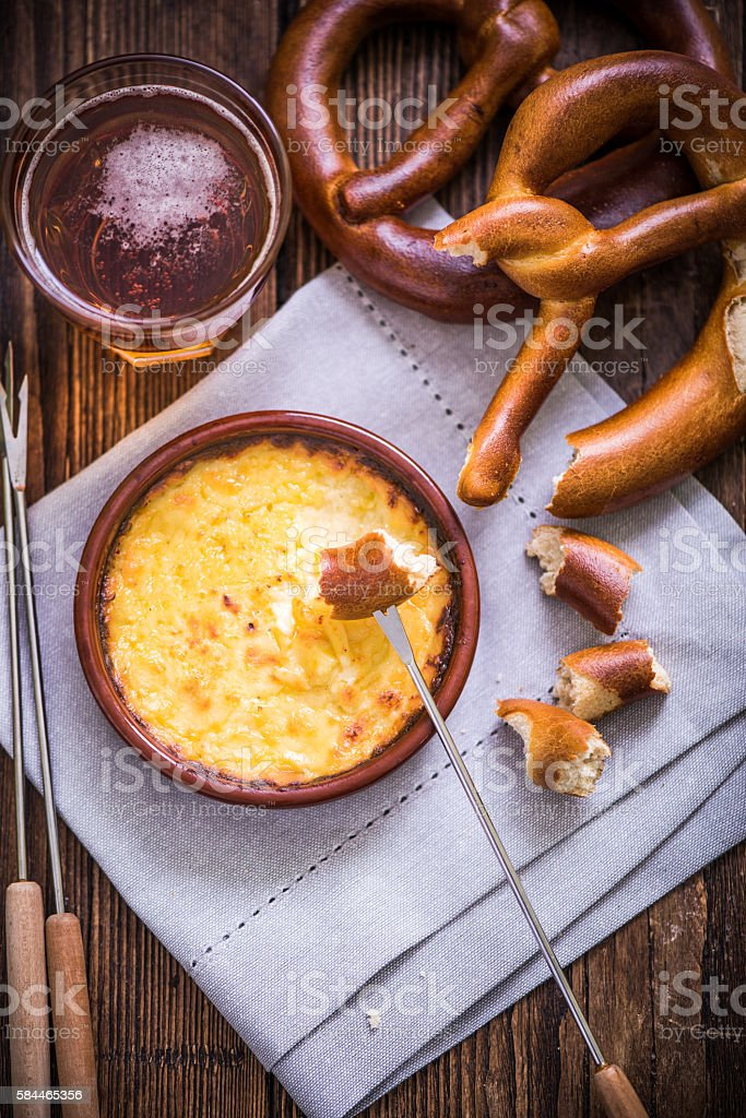 worming cheese fondue with pretzel at winter stock photo