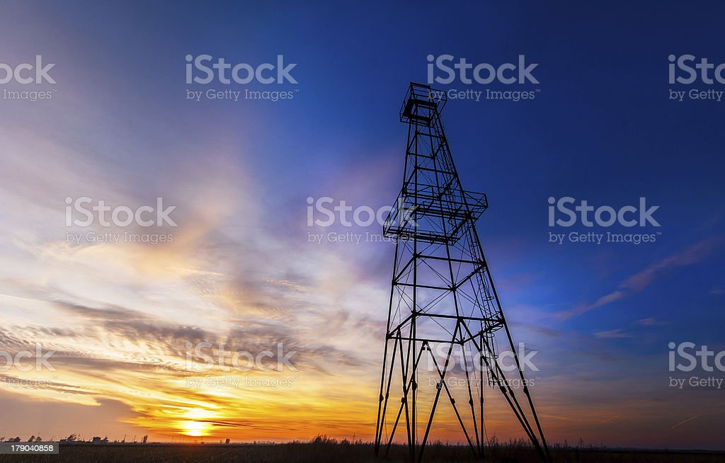 Worm's-eye view of an oil rig tower against a sunset royalty-free stock photo
