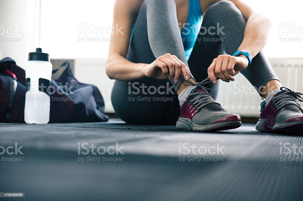 Worm's-eye view of gym floor and woman tying shoelaces stock photo
