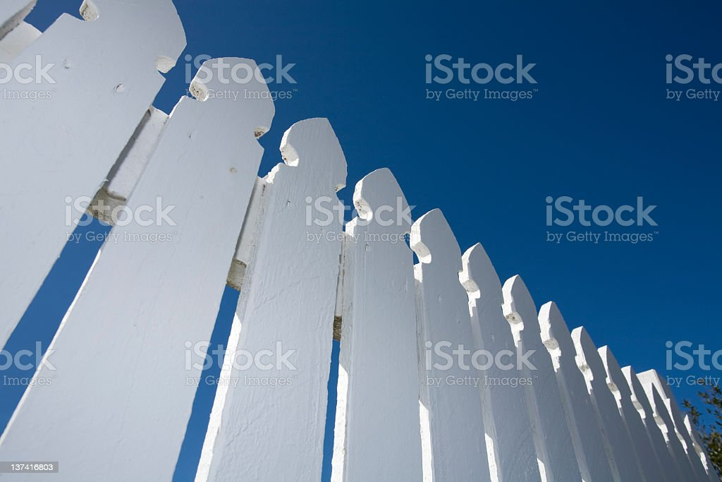 Worm's-eye view of white picket fence and blue sky royalty-free stock photo