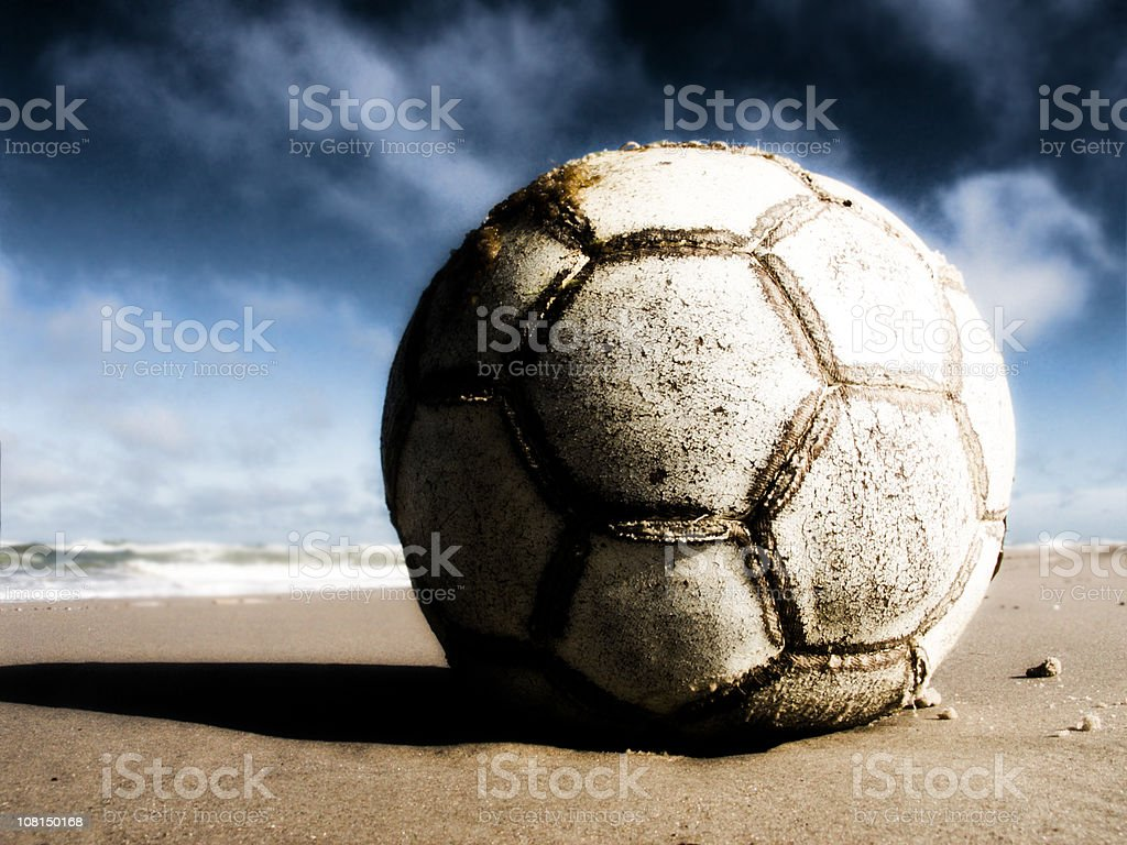 Worn and Old Soccer Ball on Sand stock photo