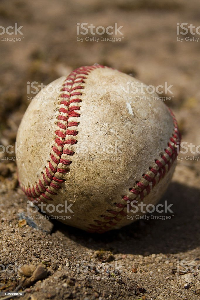 Worn baseball in dirty sand stock photo