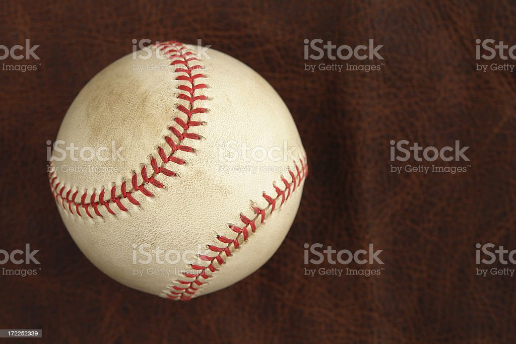 Worn baseball on old leather texture royalty-free stock photo