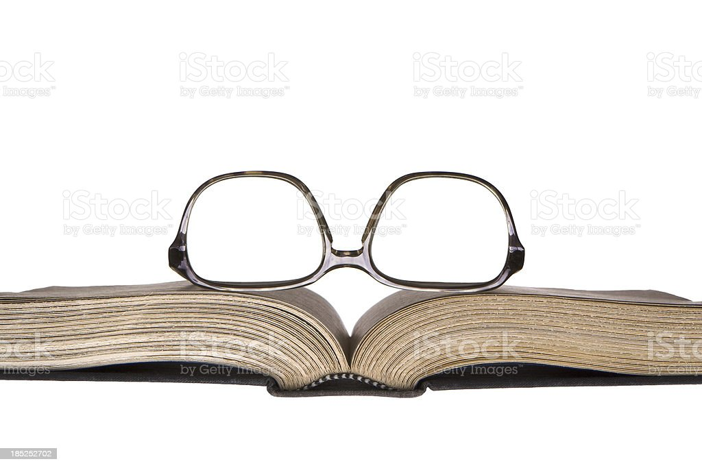 Worn eye glasses resting on old open book royalty-free stock photo