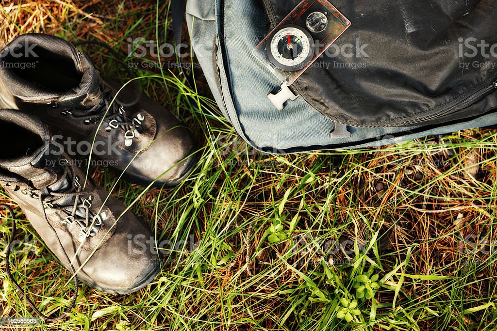 Worn hiking boots, backpack and compass in countryside stock photo