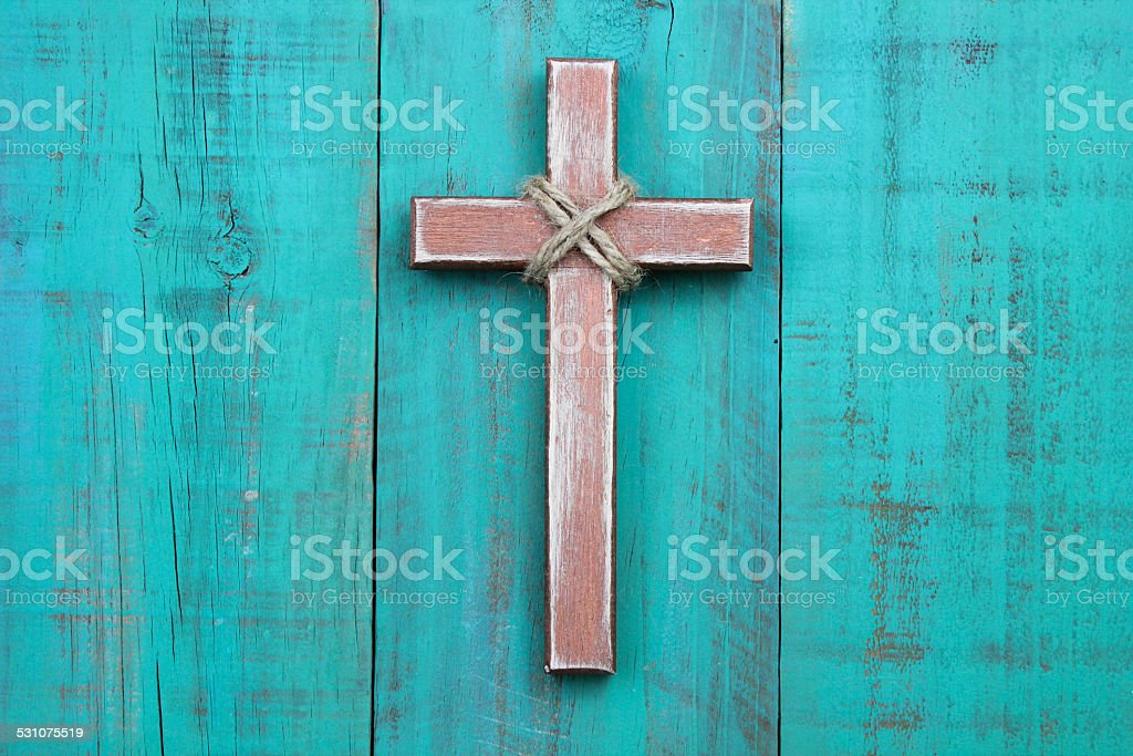 Worn wooden cross with rope hanging on teal blue background stock photo