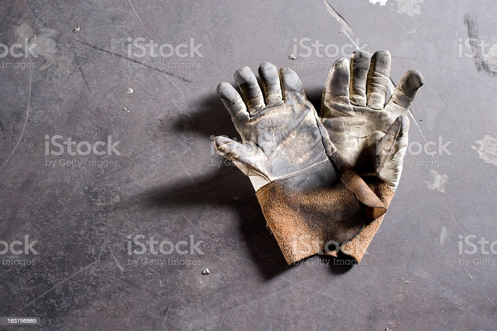 Worn work gloves lying on concrete floor stock photo