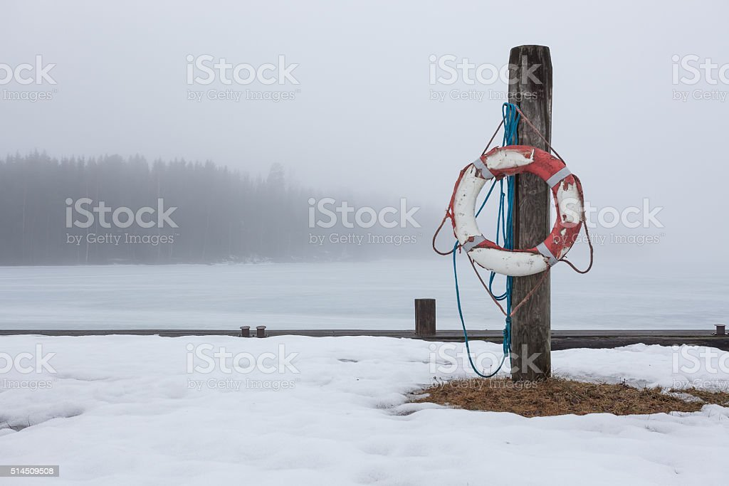 Worn-out lifesaver on post at foggy lake scape stock photo