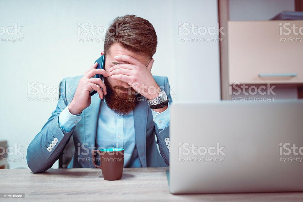 Worried and Exhausted Businessman Talking on Phone in his Office stock photo