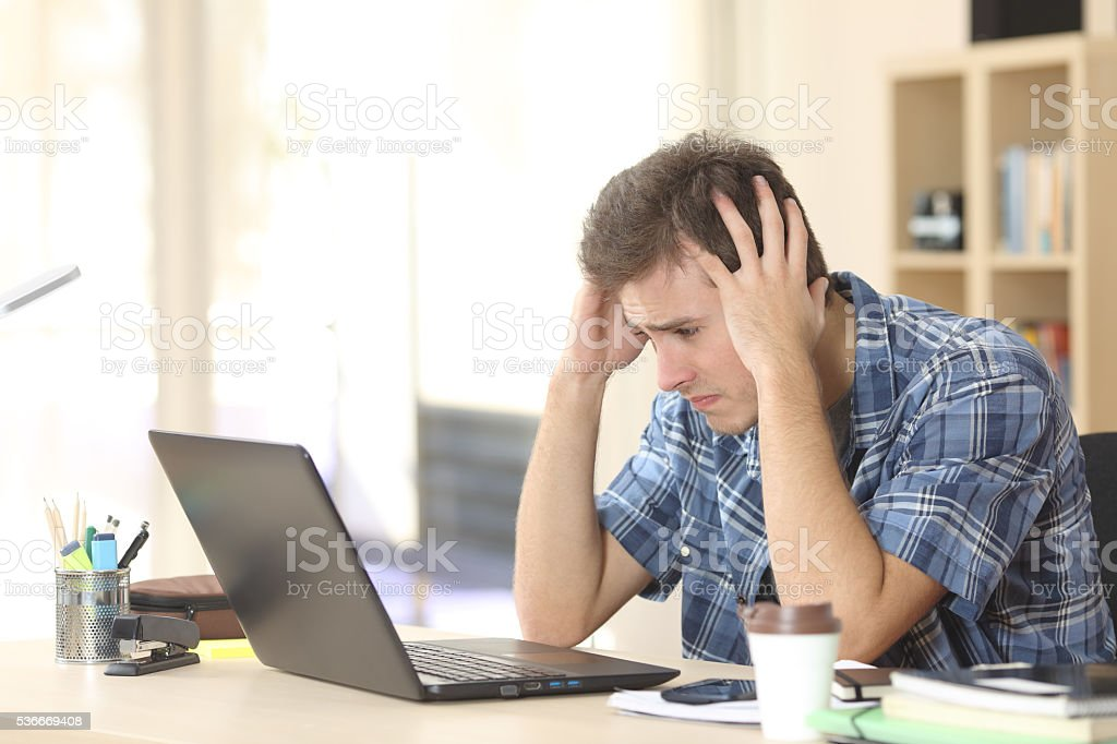 Worried and sad student watching exam results stock photo